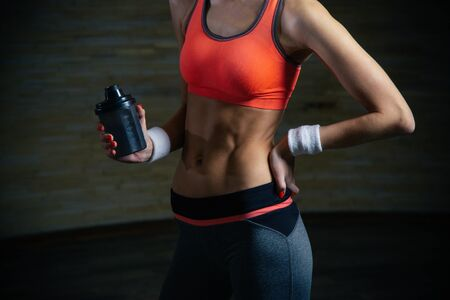 Fit lady putting one hand on the hip and holding sporty bottle Banco de Imagens