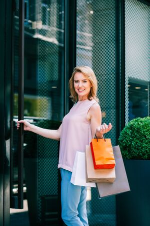 Positive woman near entrance to the shop holding paper bags