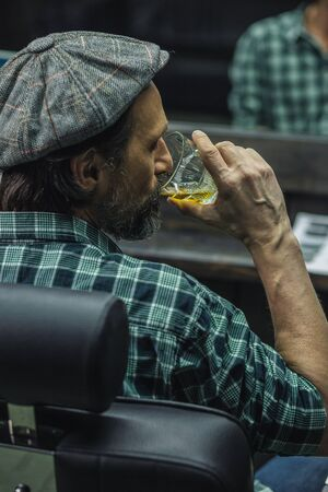 Calm man in flat hat sitting and drinking alcohol