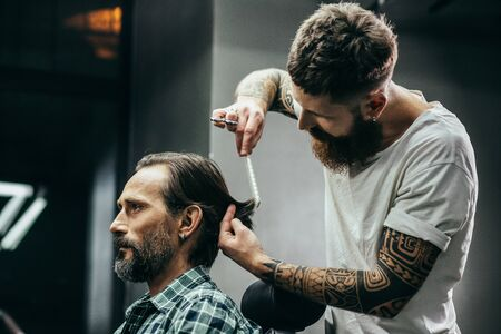 Close up of tattooed barber combing hair of calm client