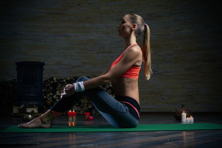 Long haired young lady sitting with straight back on the yoga mat