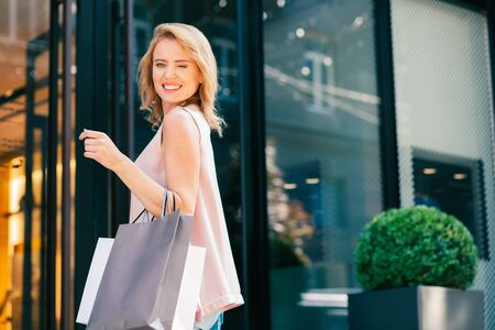 Delighted woman with shopping bags winking and smiling