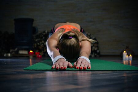 Close up of woman bending to the floor while practicing yoga asana