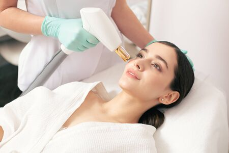 Young woman staying calm during the laser stretch mark removal Banco de Imagens