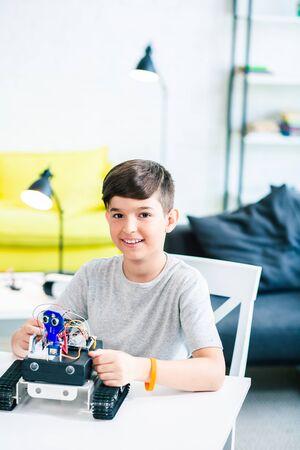 Waist up of a joyful smiling boy using robotic technologies Stock Photo - 135458460