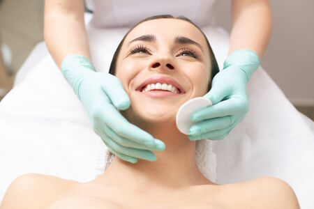 Emotional woman laughing while having her face cleaned