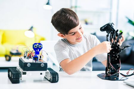 Cheerful schoolboy making experiments with his robotic device Stock Photo - 135458371