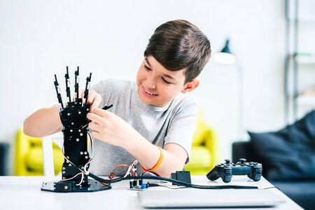 Joyful whizzkid constructing humanoid robotic hand at home Stock Photo