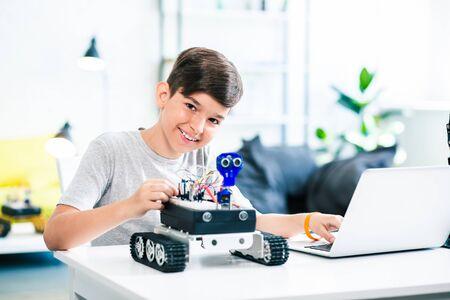 Joyful little boy testing robot while preparing for engineering classes Stock Photo - 135458151