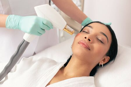 Peaceful woman closing her eyes during the modern laser treatment 스톡 콘텐츠