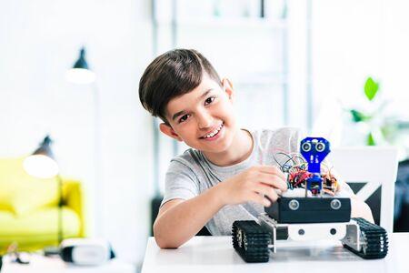 Joyful schoolboy involved in modern robotic engineering Stock Photo - 135458744