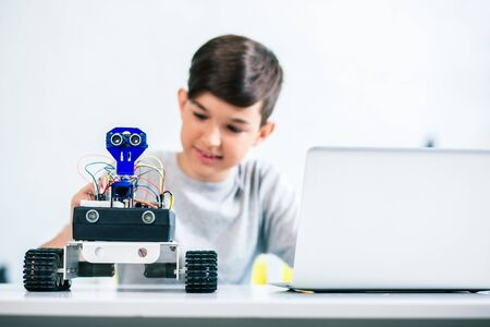 Selective focus of a robot being tested by a little boy Stock Photo - 135458541
