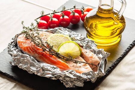 Black slate on the table with fish and lime slices in foil. Glass bottle of olive oil and branch of cherry tomatoes near
