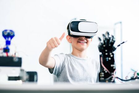 Positive ingenious boy sitting at the table while testing his humanoid robotic hand with the help of virtual reality technologies