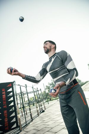 Cheerful sportsman juggling the balls and smiling