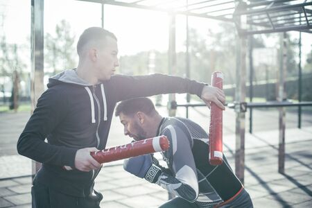 Waist up of the movement during the boxing training with boxing sticks