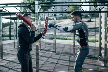 Enthusiastic boxer training outdoors and mastering his punches