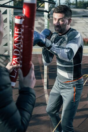 Skilled sportsman making the punch during boxing training outdoors