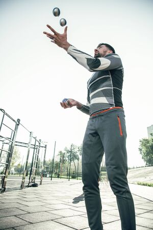 Bearded sportsman looking at the balls while juggling Banque d'images