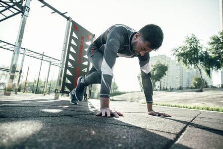 Concentrated professional sportsman having training at the sports ground and doing pushups while being alone