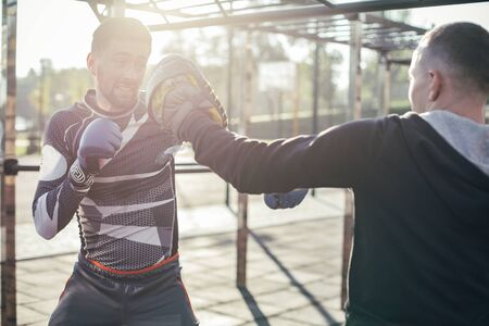 Young man wearing focus mittens and professional MMA boxer mastering his punches