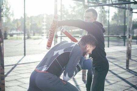 Pugile attento che padroneggia le sue posizioni evitando i pugni davanti ai bastoni da boxe nelle mani del suo allenatore