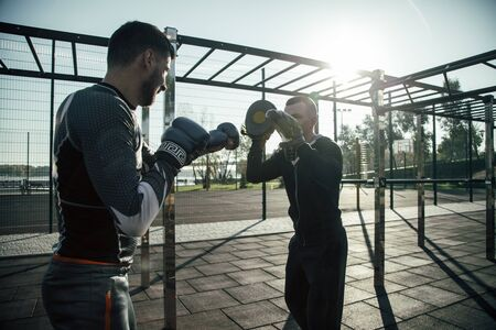 Confident MMA champion looking at the trainer while practicing punches with focus mitts