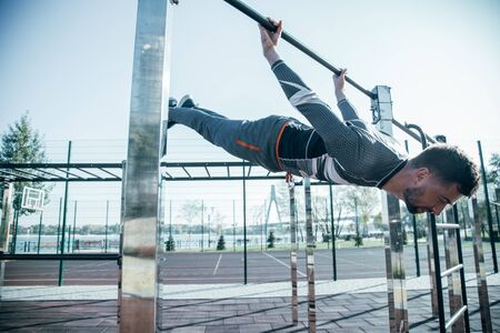 Calm experienced sportsman closing his eyes and looking peaceful while doing the chin ups Zdjęcie Seryjne