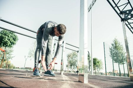 Experienced professional sportsman having morning exercises and bending down while trying to touch his feet