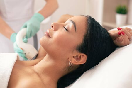 Young beautiful woman lying with her eyes closed and smiling while undergoing laser hair removal on her armpit Banco de Imagens