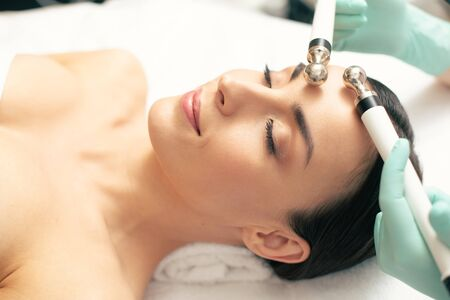 Peaceful woman closing her eyes during the microcurrent therapy