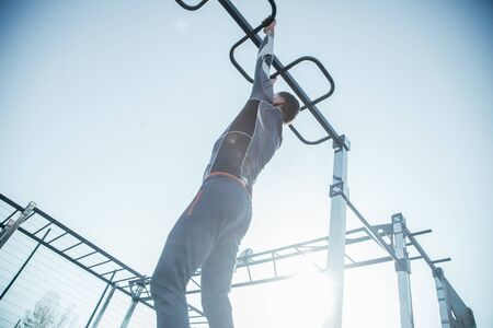 Laconic photo of young man in sporty clothes hanging on the chin ups bar while being at the sports ground during his training