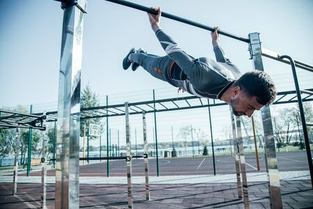 Relaxed sportsman closing his eyes while doing the exercises on chin ups bar at the sports ground Stockfoto