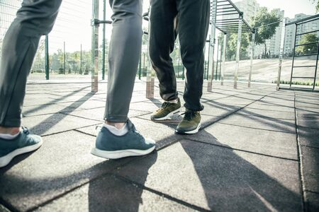Close up of the feet of two sportsmen standing opposite each other at the sports ground while having their training outdoors Banco de Imagens
