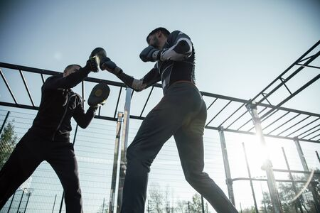 Laconic photo of young MMA boxer standing at the sports ground with his trainer and practicing punches on focus mitts Banco de Imagens