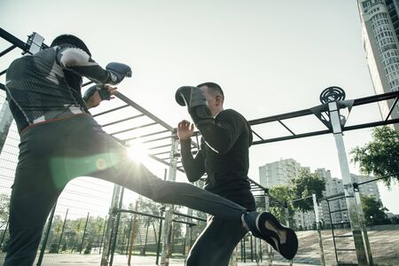 Enthusiastic MMA champion practicing leg punches with his trainer while being at the sports ground with him Banco de Imagens