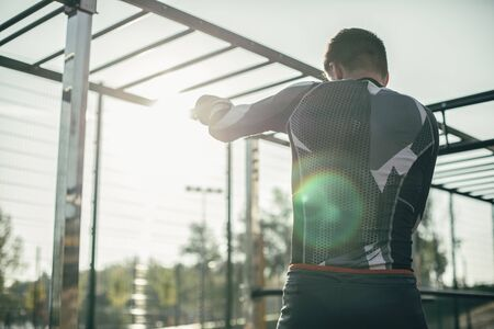 Concentrated professional MMA champion being at the sports ground alone and putting one hand up while practicing the stances