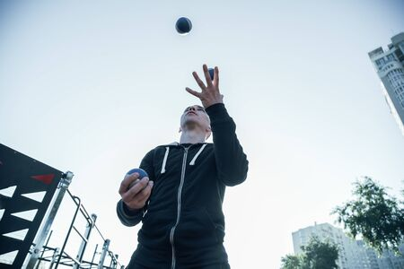 Calm sportsman throwing balls into the air and catching them