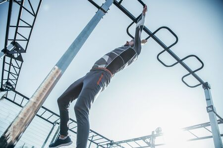 Confident strong sportsman being at the sports ground alone and carefully climbing the chin ups bar while having his training Banco de Imagens