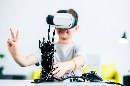Selective focus of a robotic hand standing on the table while a positive ingenious boy experimenting with it
