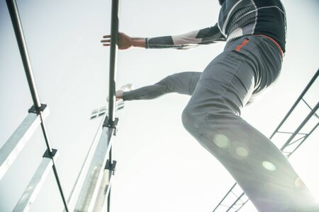 Professional sportsman having training outdoors and training his leg muscles while putting on foot on the chin up bar