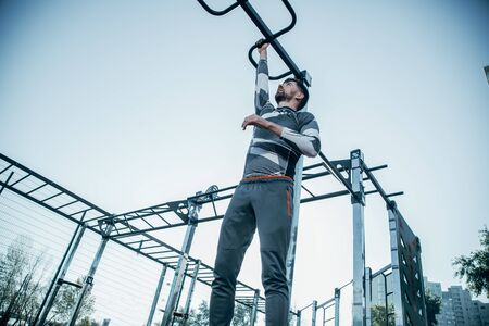 Serious strong sportsman looking up while putting one hand on the chin up bar while hanging from it
