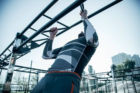 Strong sportsman training his muscles and doing chin ups Banco de Imagens