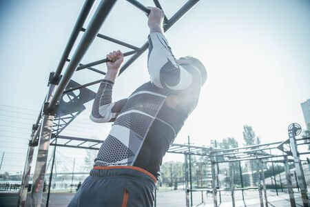 Waist up of young man doing chin ups on the bar outdoors Banco de Imagens