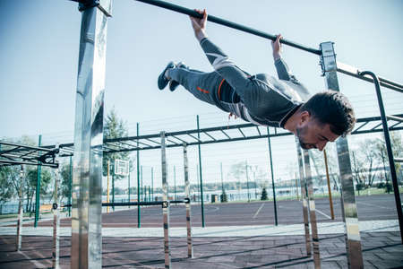 Calm sportsman hanging from the chin up bar and closing his eyes Banco de Imagens