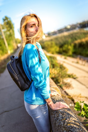 blusa: chica rubia con estilo joven en blusa turquesa y una mochila negro sobre perapet oblakotilas manos, cara de niña cierra un mechón de pelo Foto de archivo