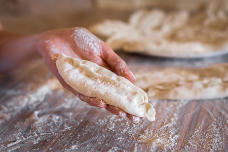 patty of raw dough in a female hand