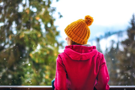 snowy weather, girl standing back in the winter, in the yellow and red knitted hat sports hooded sweatshirt. He is looking at the snow Stock Photo