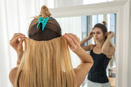 girl tries on blonde false hair strands on clips. Artificial hair extension Zdjęcie Seryjne