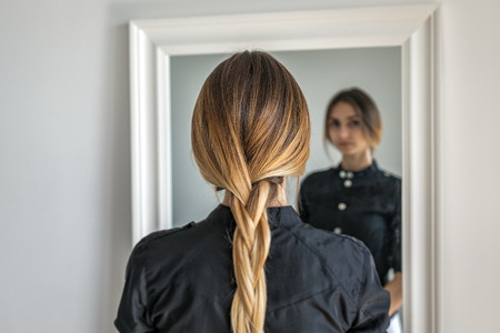 woman girl with ombre hairstyle in braid in front of mirror Stock fotó